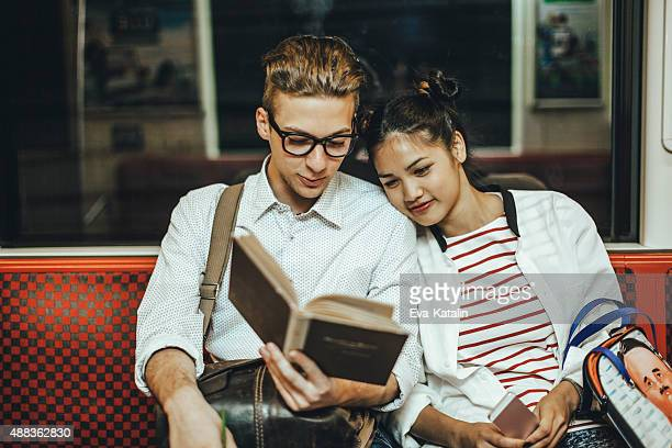Young couple reading a book on the underground