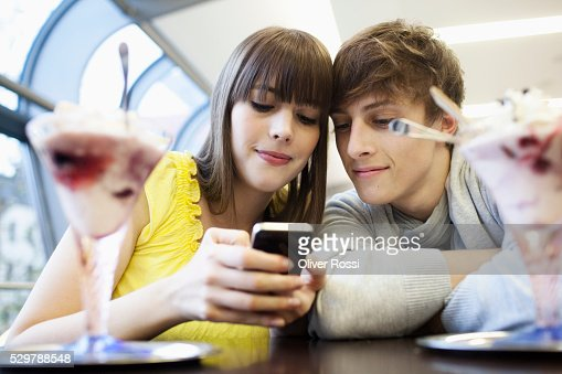 Young couple reading a text message : Bildbanksbilder