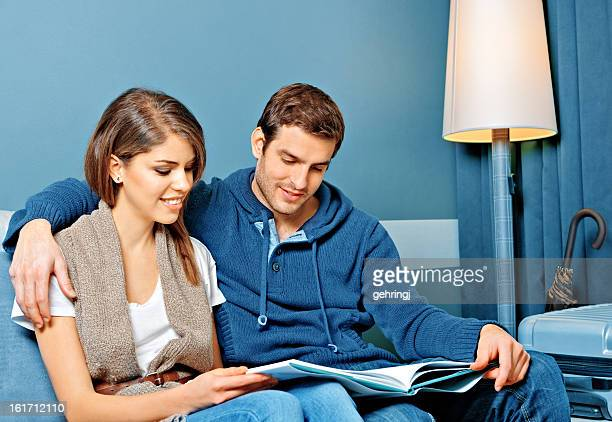 Young couple reading in a hotel room