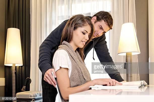 Giovane coppia leggendo in una camera d'hotel