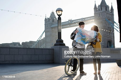 Young couple reading map by Tower Bridge, London, England