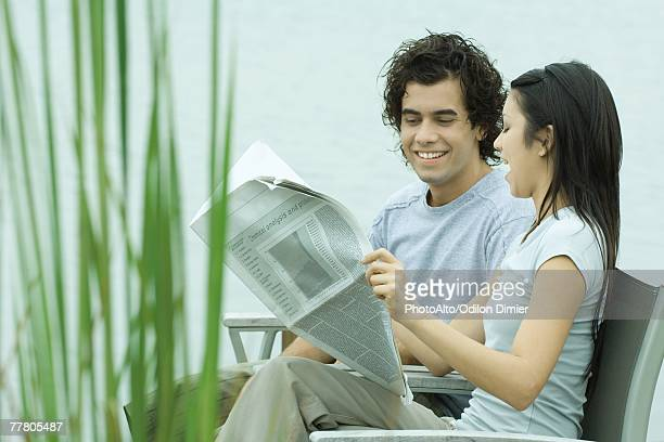 Young couple reading newspaper together by edge of lake