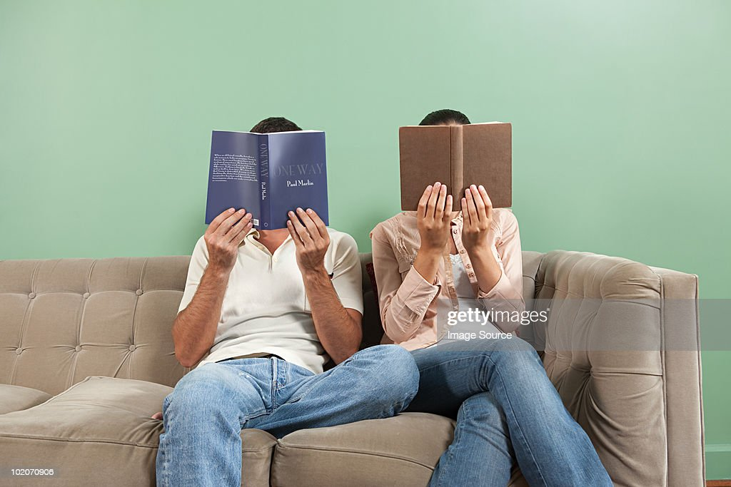 Young couple reading with books obscuring faces : Stock Photo