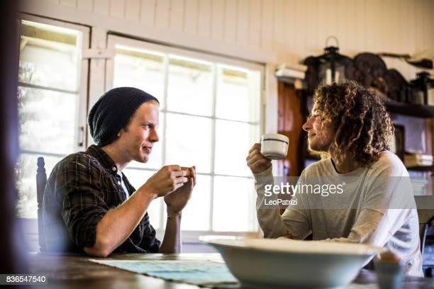 Junges Paar entspannen und genießen Sie einen heißen Kaffee in Hütte in den Bergen