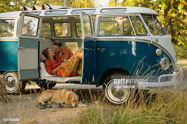 A young couple relax inside a classic van with their dog.