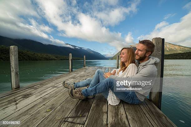 Young couple relaxes on lake pier, morning sunlight