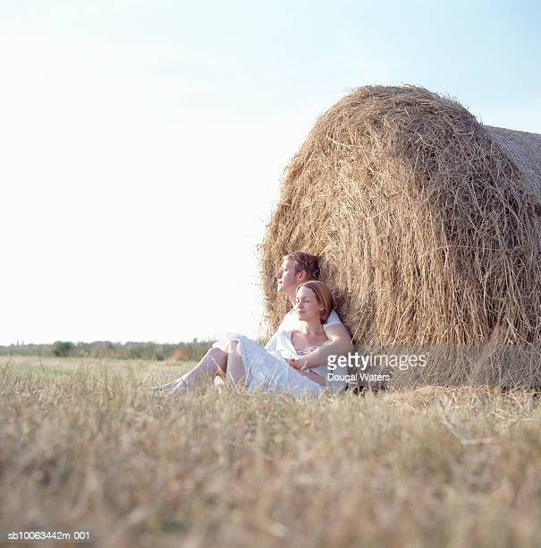 Young couple relaxing against straw bale