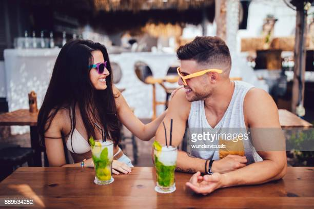 Young couple relaxing and drinking cocktails at summer beach bar