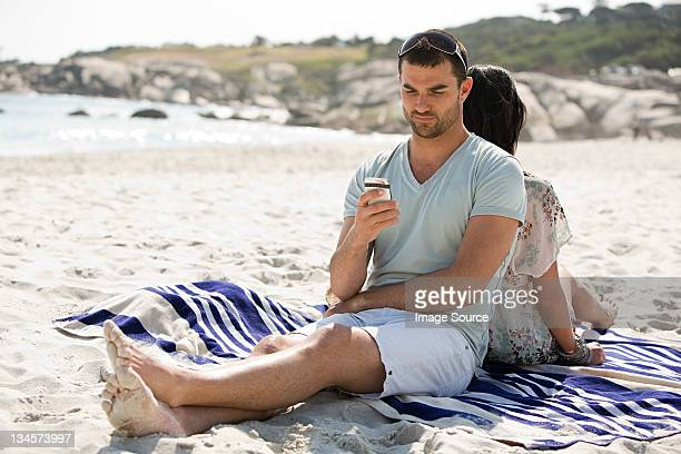 Young couple relaxing back to back on a beach