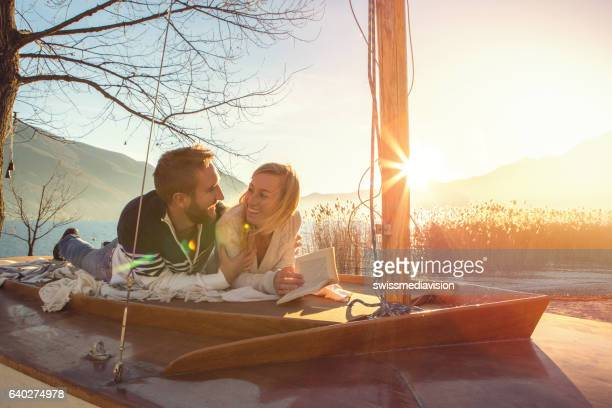 Young couple relaxing by the lake reading book
