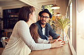 Portrait of young man and woman sitting at a cafe and talking. Young couple relaxing in a coffee shop.