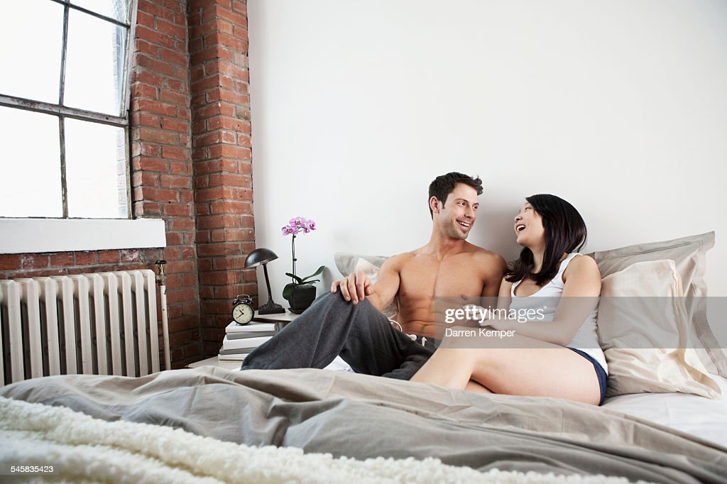 Young couple relaxing in bed : Bildbanksbilder