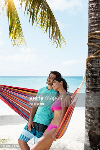 Young couple relaxing in hammock on beach : Foto de stock