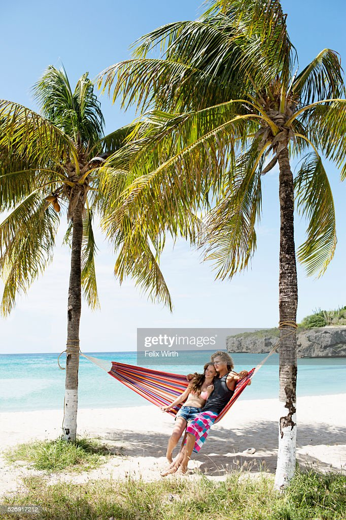 Young couple relaxing in hammock on beach : ストックフォト