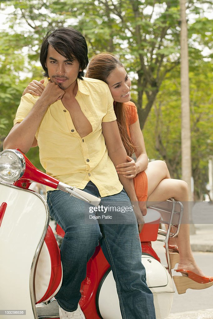 Young couple relaxing on classic scooter : Stock Photo