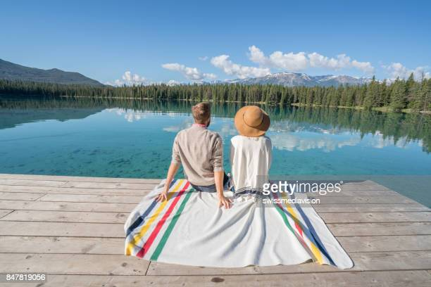 Young couple relaxing on lake pier, Canada