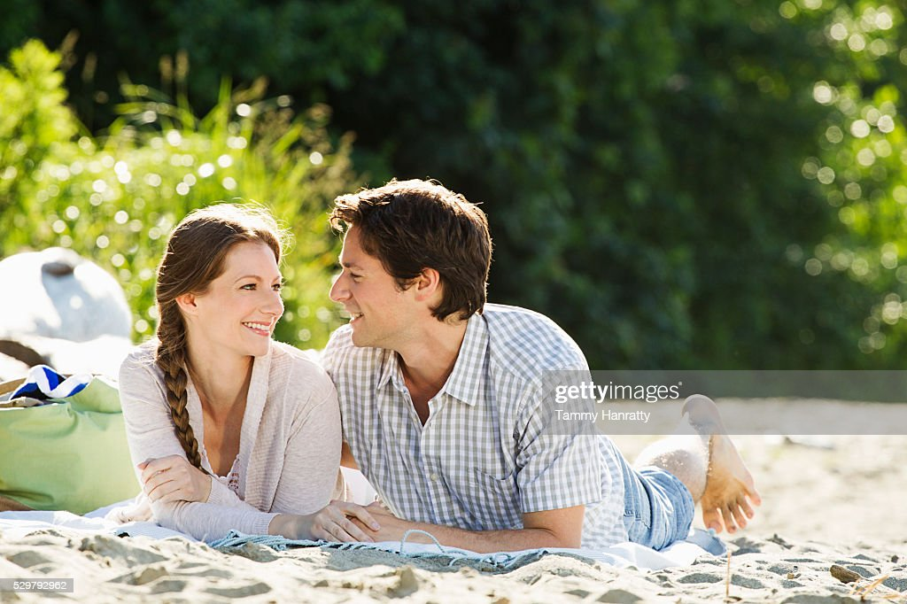 Young couple relaxing on sand outdoors : Stock Photo