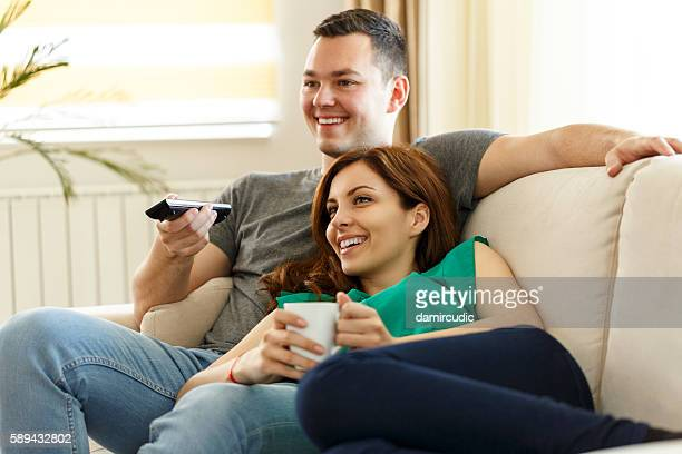 Young couple relaxing on sofa and watching television together