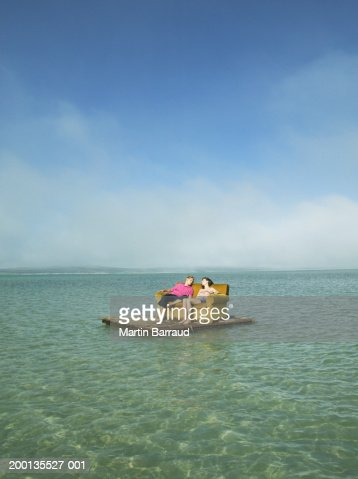Young couple relaxing on sofa on raft at sea