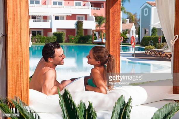 Young couple relaxing on sunlounger at holiday resort