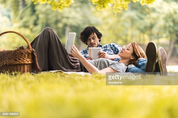 Young couple relaxing with books on picnic during springtime.
