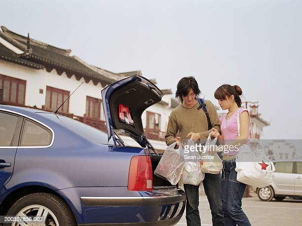 Young couple removing shopping bags from car's trunk