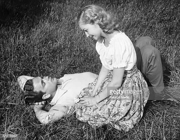 Young couple resting on lawn, (B&W)