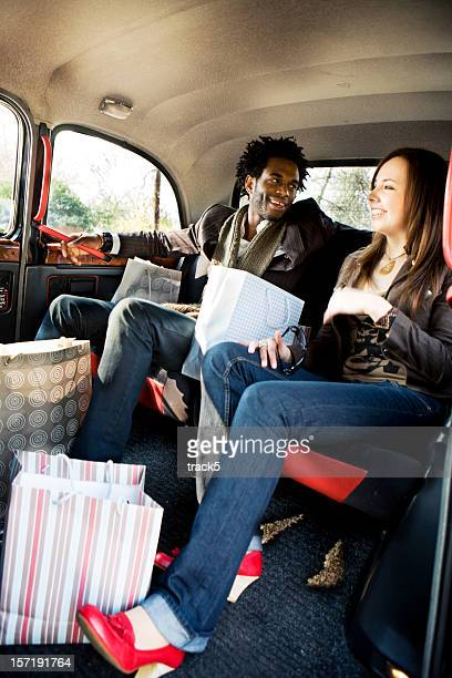 Young couple returning home in a London taxi after shopping