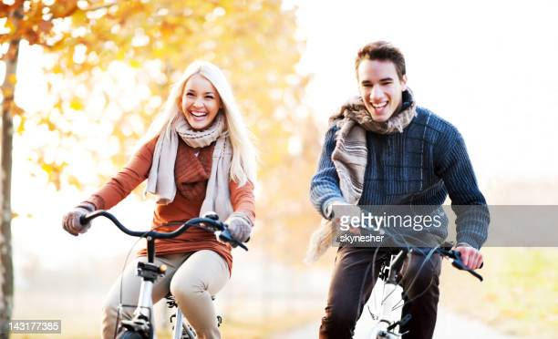Young  couple rides bikes on a beautiful autumn day.
