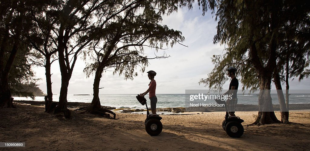 A young couple rides segways together by the ocean : Stock Photo