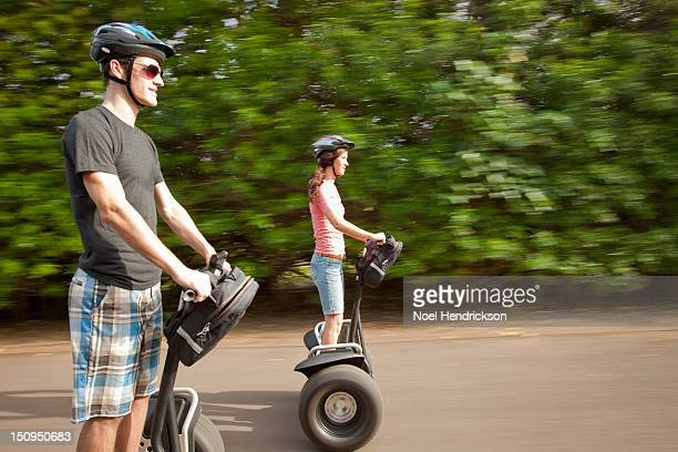 A young couple rides segways together