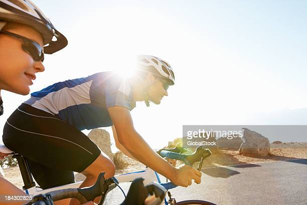 Young couple riding bicycles in the countryside