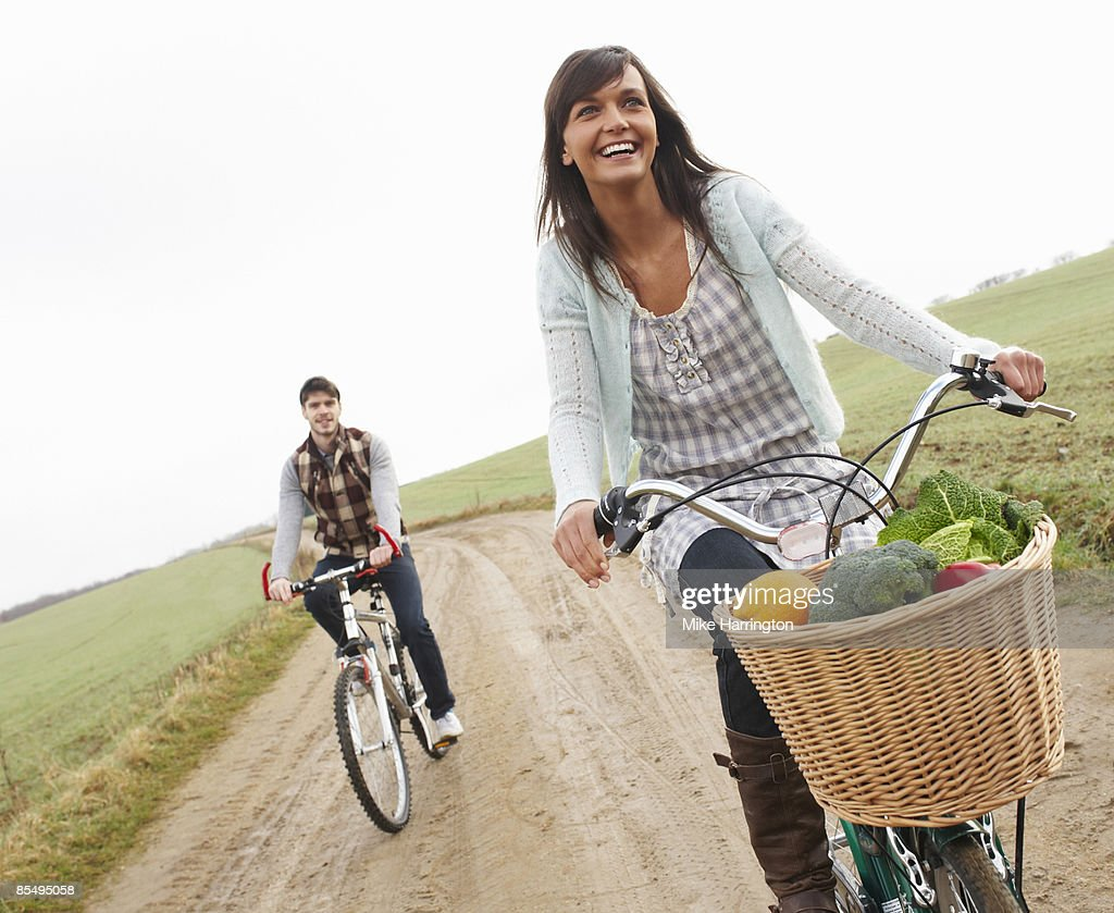 Young couple riding bikes with shopping : Stock Photo