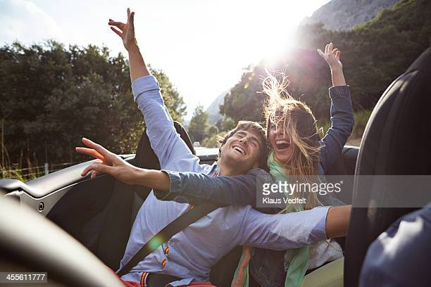 Young couple riding car, wind in hair