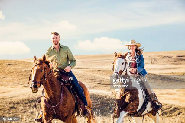 Young Couple Riding Horseback Together