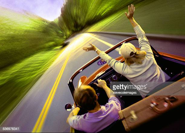 Young couple riding in a convertible on highway.