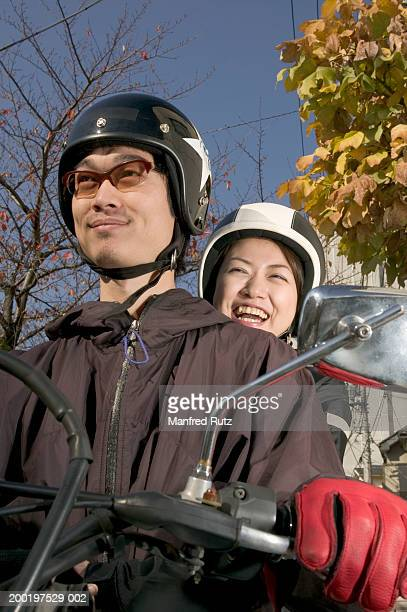 Young couple riding motorcyle wearing helmets, smiling