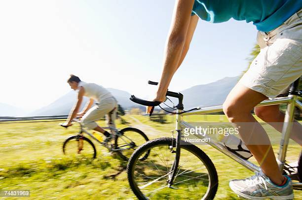 Young couple riding mountain bike, side view, (blurred motion)