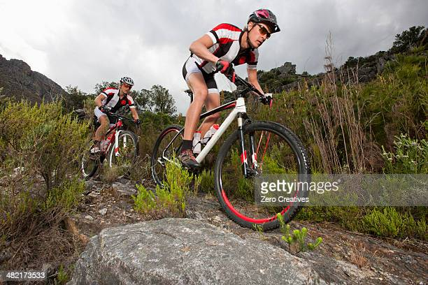 Young couple riding mountain bikes on dirt track