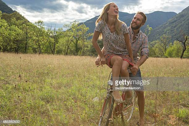 Young couple riding on a vintage bicycle in the countryside