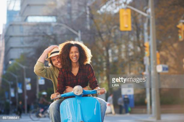 Young couple riding scooter