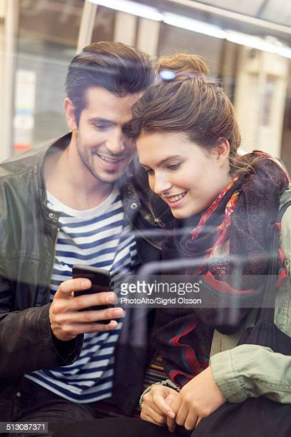 Young couple riding subway looking at digital tablet together