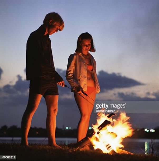Young Couple Roasting Hotdogs Over Beach Bonfire
