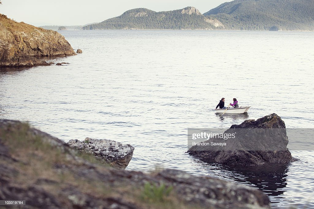 A young couple row out into the Puget Sound from Orcas Island in a small row boat.
