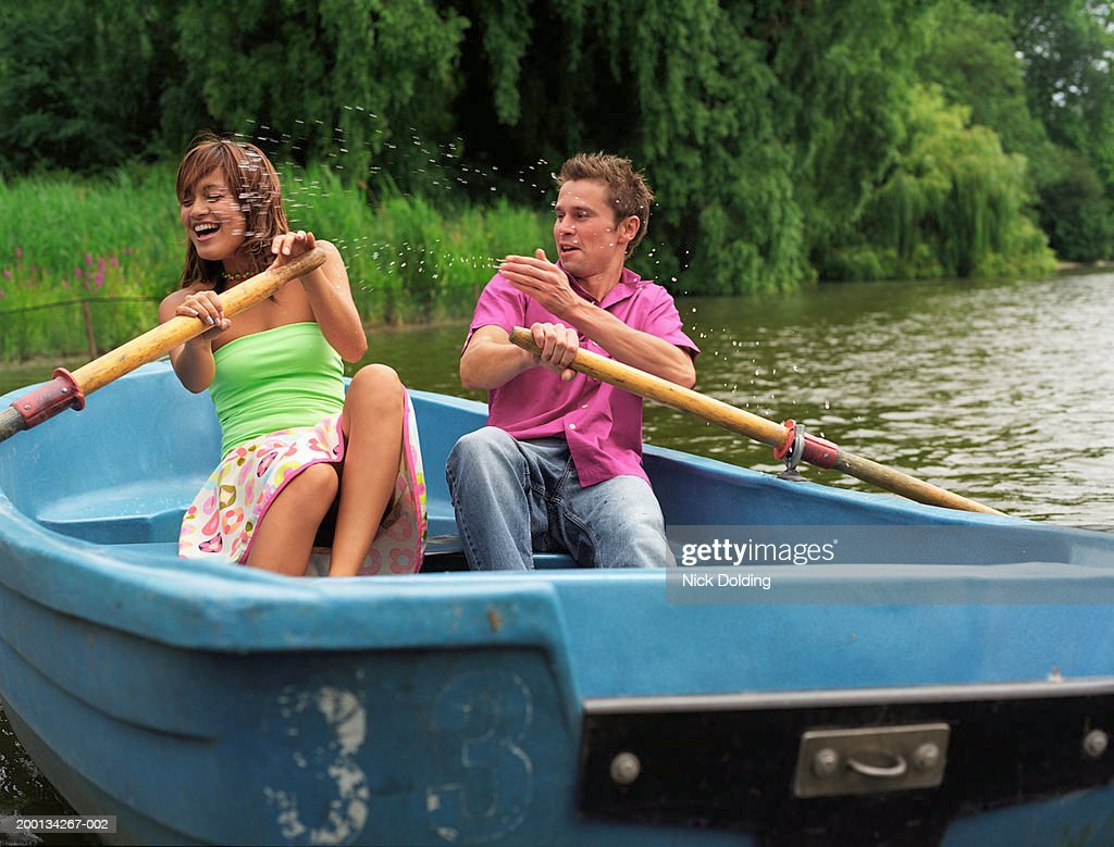 Young Couple Rowing Boat On Lake Man Splashing Water Over ...