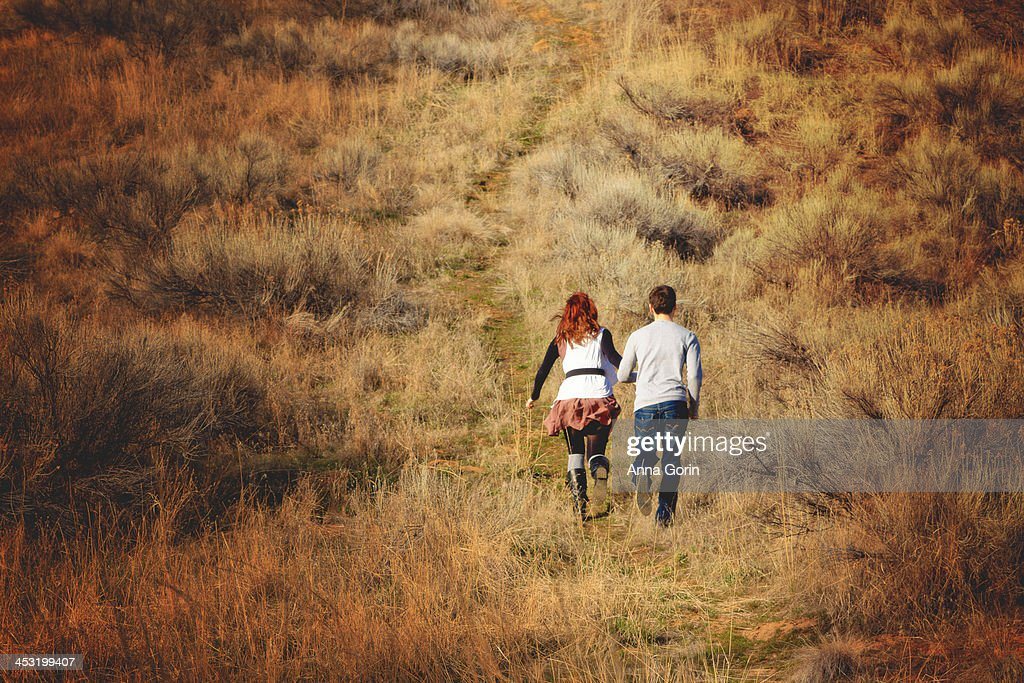 Young couple run up hill, holding hands