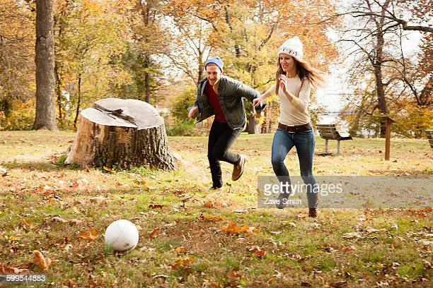 Young couple running after soccer ball in autumn park