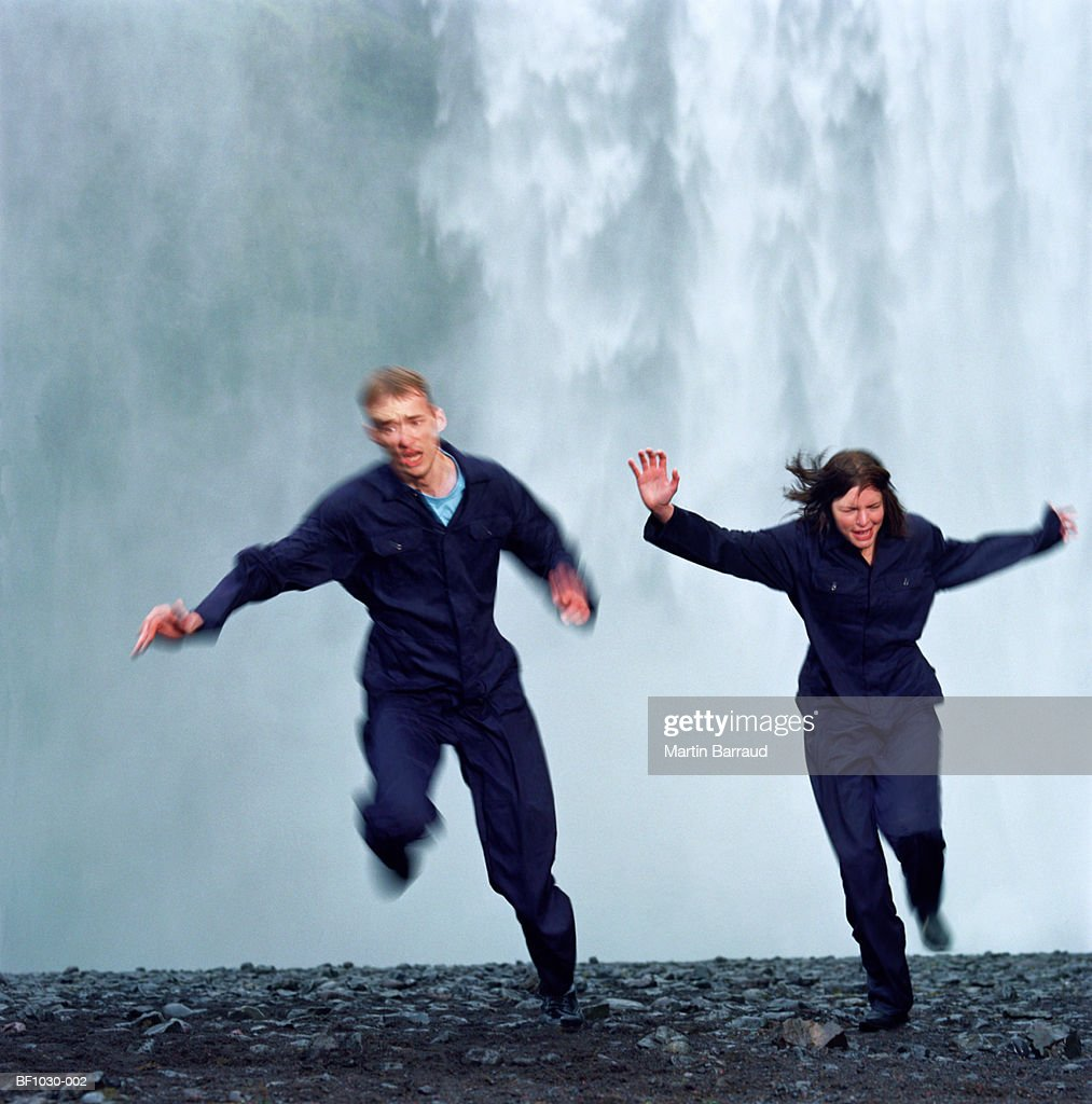 Young couple running away from waterfall (blurred motion) : Stock Photo