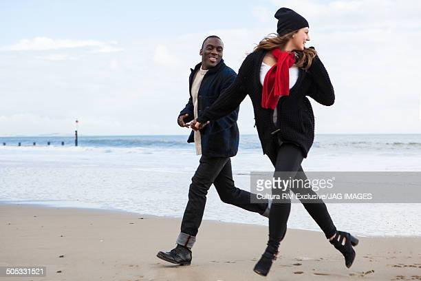 Young couple running from sea, Bournemouth, Dorset, UK