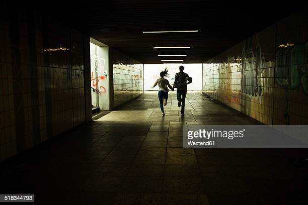 Young couple running hand in hand in a dark underpass, partial view
